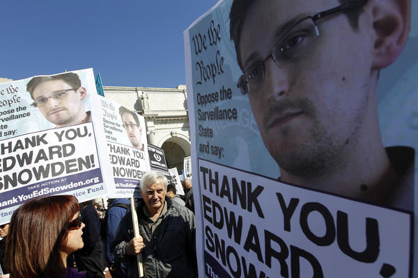 Demonstrators applaud NSA leaker Edward Snowden at a protest in Washington, D.C., on Saturday against broad NSA surveillance of Americans and U.S. allies.