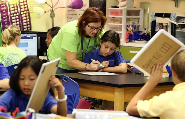 Carolyn Rethwisch, a math teacher, works with student Stephanie Monsalve, 11, on Friday, October 25, 2013. Galileo School for Gifted Learning plans to open a middle school next year, one of a small number of charter operators to gain approval to open a new school in Central Florida next year.