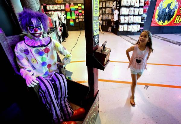 7-year-old Alexis Kimble of Orlando delights in seeing the scary clowns on display at the Spirit Halloween store in Orlando, Monday, October 28, 2013. The economy is spooking some consumers away from spending what they did in 2012.
