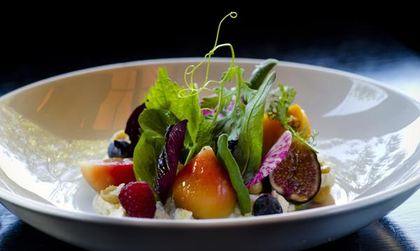 A colorful dish of beets and sliced berries decorated with fronds, tendrils and leaves by chef Chris Jacobson.