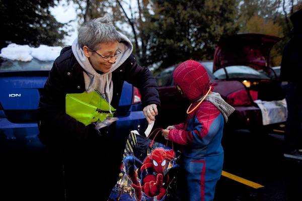 Sandy Reeves gives 4-year-old Xavier Pani candy and a Stand for the Silent bookmark, an anti-bullying organization, during Spookalooza at the Schaumburg YMCA on Oct. 19.