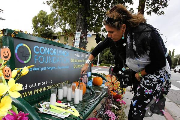 Jeri Dye Lynch lights a candle at a bus stop bench at Woodman and Addison avenues. Three years ago, her son Conor Lynch was struck and killed in a hit-and-run accident near the intersection.