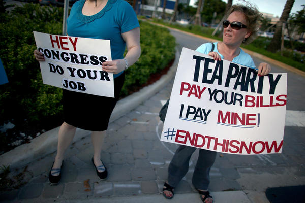 "Haydee Perkal holds a sign reading, ""Tea Party Pay Your Bills I Pay Mine!"" as she and others gather in front of the office of Rep. Mario Diaz-Balart (R-FL) and Sen. Marco Rubio (R-FL) to protest against the partial government shutdown on October 15, 2013 in Doral, Florida. In Washington, DC Congress and the White House continue to work on a budget deal to get the government fully operational."