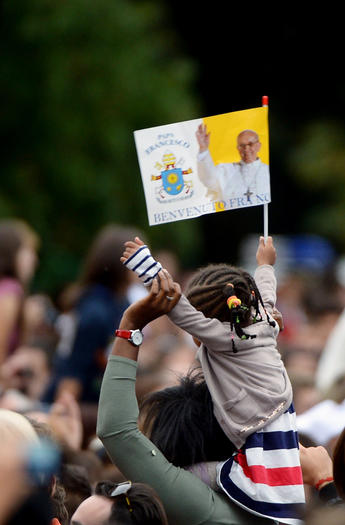 A little girl waves a flag as she waits for the arrival of Pope Francis.