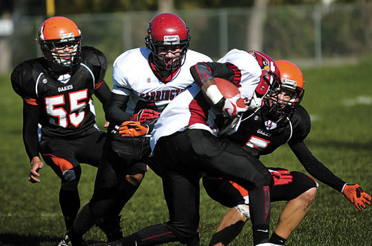 Ethan Zetocha (5) of Oakes prepares to tackle a Carrington runner as Zetochas teammate Scott Ketterling (55) moves in on the play.