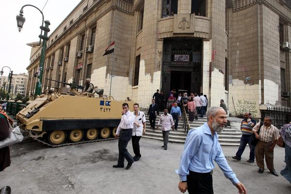 An Egyptian army tank is stationed outside the high court during the trial of Muslim Brotherhood leaders in Cairo on Tuesday. Judges overseeing the trial withdrew from the case.