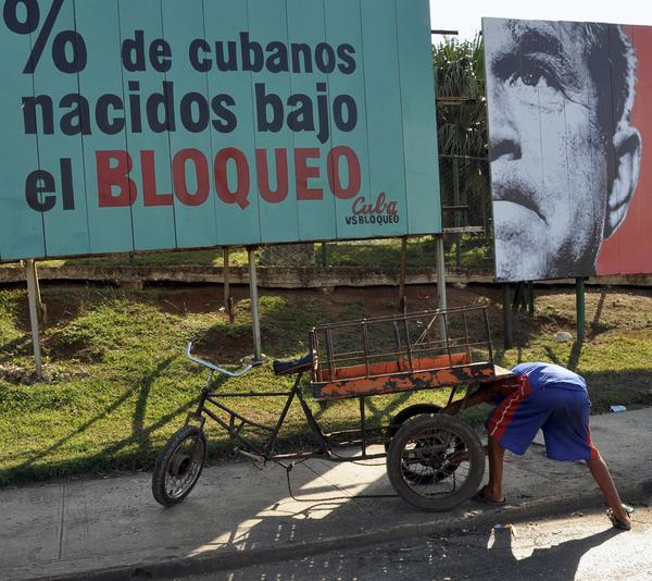 A Cuban repairs his tricycle in front of a political poster allusive to the US embargo on Cuba in Havana. The US economic embargo on Cuba has been in place since 1962.