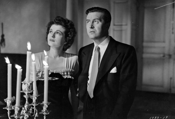 "Ray Milland as Roderick Fitzgerald and Ruth Hussey as Pamela Fitzgerald in the film ""The Uninvited."""