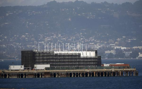 Speculation is rampant about the top-secret, four-story structure that has been erected atop a huge barge, now sitting next to a pier at Treasure Island in the middle of San Francisco Bay.