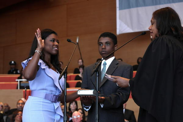 Stephanie Neely is sworn in as city treasurer with her son Justin holding the Bible during a public ceremony at Millennium Park in May 2011. (Nancy Stone/ Chicago Tribune)