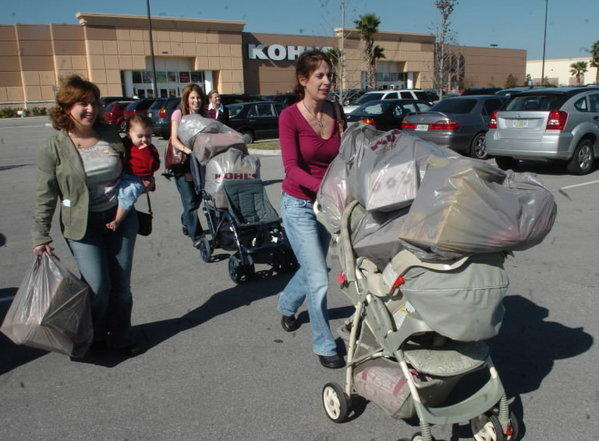 Sisters Holly Graham, right, and Betsy Kleiman, center, push strollers full of purchases from Kohl's at the Loop shopping area on Black Friday in 2006.