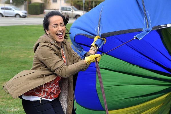 6th grade math and science teacher Catherine Eskandar is caught in a fan blast of air that was used to inflate a hot air balloon that she and fellow 6th grade teacher Sarah Reed float in above about 300 6th grade students at Jordan Middle School in Burbank on Monday, October 28, 2013. The balloon, with a capacity equal to 77,000 basketballs, was provided by Details Above All Hot Air Balloons to give 6th graders a live demonstration of a balloon in flight.