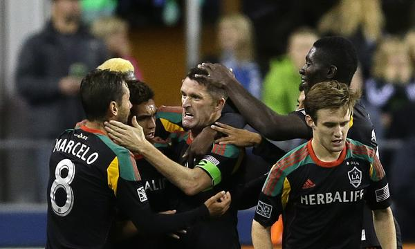 Galaxy forward Robbie Keane, center, celebrates with his teammates after scoring a goal against the Seattle Sounders on Sunday. The Galaxy open the playoffs Saturday against Real Salt Lake.