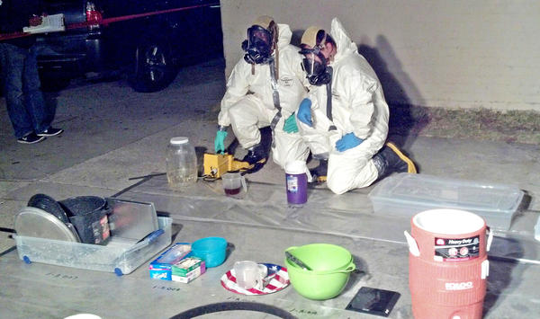 Detectives investigate an alleged methamphetamine lab, which was discovered in a home in Huntington Park.