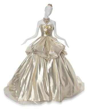This dress has a bodice of gold silk and laces in the back. Featured is a gold-tone metal tiara and bib-style necklace inlaid with crystals, both with Medusa motif.