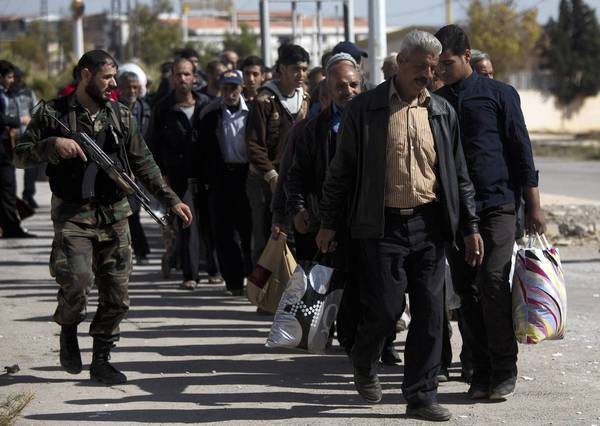 A Syrian soldier escorts men arriving from the rebel-held suburb of Muadhamiya to Damascus. The suburb, which is under government siege, has been cut off from food and medicines for months.