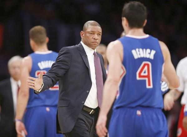 Clippers Coach Doc Rivers congratulates guard J.J. Redick as he walks toward the bench during a stoppage in play during the first half of the team's regular-season opener against the Lakers on Tuesday.