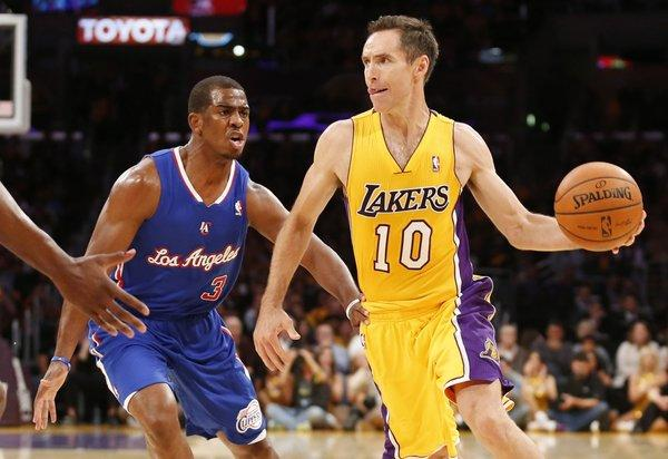 Steve Nash, right, passes the ball as Chris Paul defends during the regular-season opener for the Clippers and Lakers at Staples Center on Tuesday.