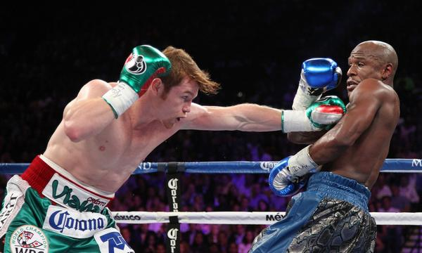 'Canelo' Alvarez, left, throws a punch during his majority decision loss to Floyd Mayweather Jr. in September. Alvarez's next bout could come against Miguel Cotto in March.