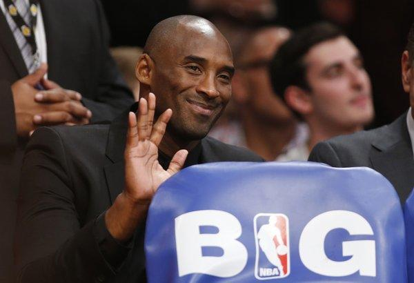 Kobe Bryant waves from behind the Lakers' bench during the team's home opener against the Clippers at Staples Center on Tuesday.
