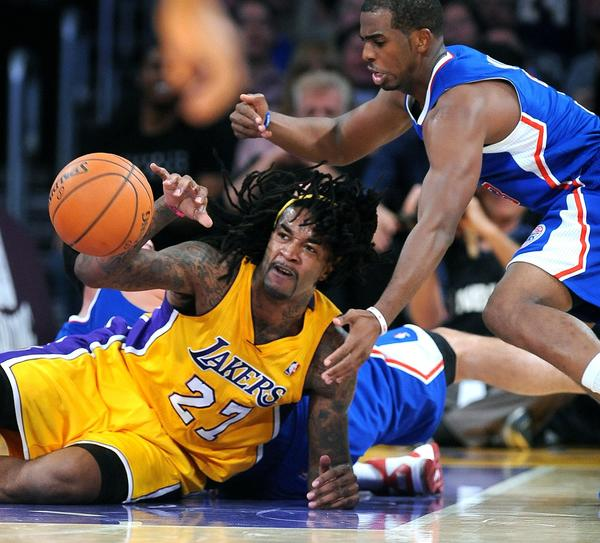 Jordan Hill gets control of a loose ball in front of Chris Paul during the Lakers' 116-103 home-opening win over the Clippers on Tuesday.