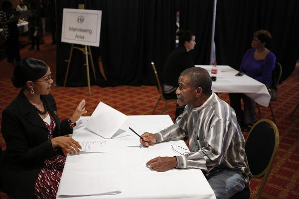 A hotel manager, left, interviews with a job seeker during a job fair at a hotel in Louisville, Ky.