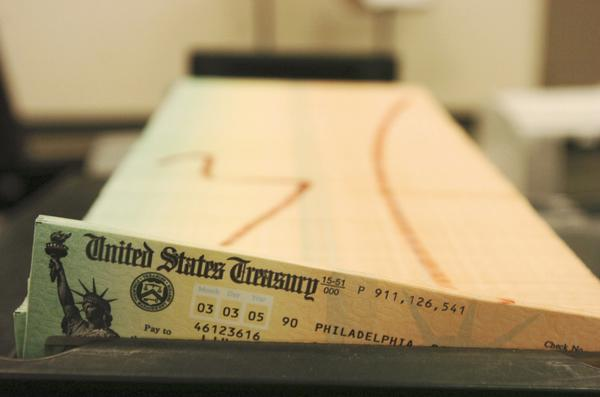 Monthly Social Security payments will rise 1.5% due to a cost of living adjustment, the Social Security Administration announced Wednesday. Above,trays of checks waiting to be mailed.