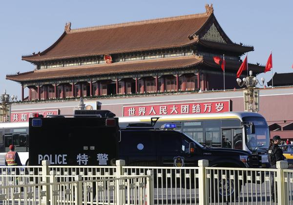 A police vehicle is parked on a road fronting the Forbidden City at Beijing's Tiananmen Square on Tuesday. On Monday, a car crashed through barriers, plowed into a crowd of tourists and police, and burst into flames in the square, killing five people.