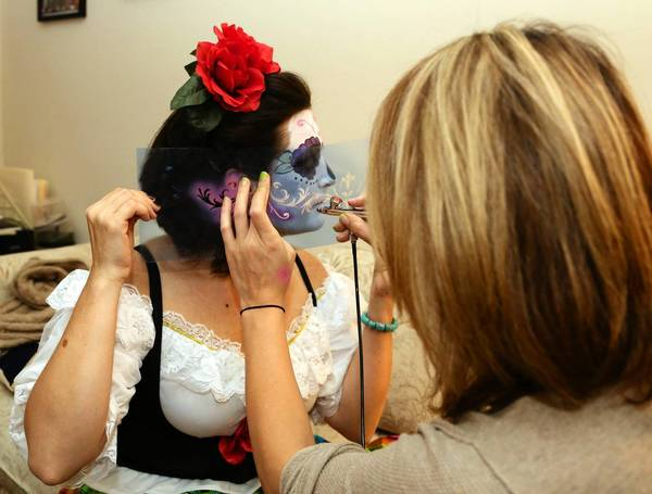 Makeup artist Lexi Martinez transforms Sherri Pontious into a Day of the Dead skeleton, using an airbrush and stencil to place the designs.