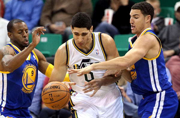 Golden State's Andre Iguodala, left, and Klay Thompson try to steal the ball from Jazz center Enes Kanter during a preseason game.