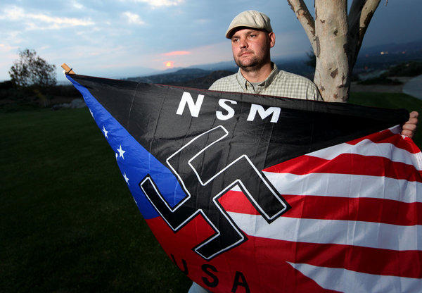 Jeffrey Hall holds a neo-Nazi flag near his Riverside home. He was killed by his then-10-year-old son, who will be placed either in state-run juvenile custody or a rehabilitation facility.