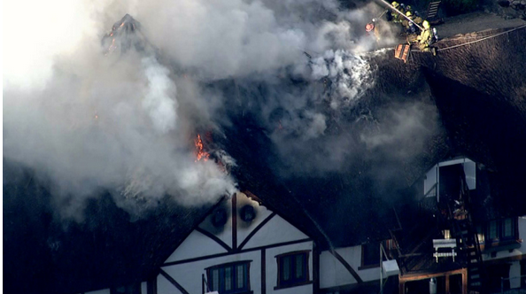 Firefighters battle a blaze at a large Encino home.