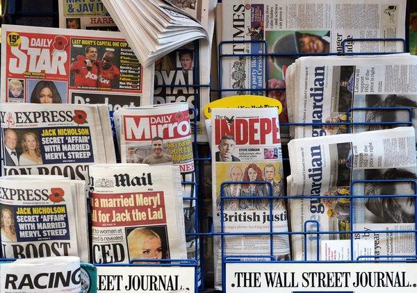 Newspapers on a rack at a newsstand in London on Wednesday. A group of publishers failed in its attempt to block a press regulation charter.