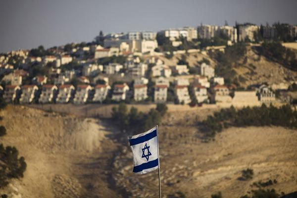 An Israeli flag flies in front of the West Bank settlement of Maaleh Adumim on the outskirts of Jerusalem.