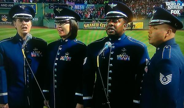 "Master Sgt. Jennifer Dashnaw, Staff Sgt. Rachel Webber, Tech. Sgt. Niko Ellison, and Tech. Sgt. Quez Vasquez of the Air Force Heritage of America Band sing ""God Bless America"" during the seventh-inning stretch of Game 6 of the World Series."
