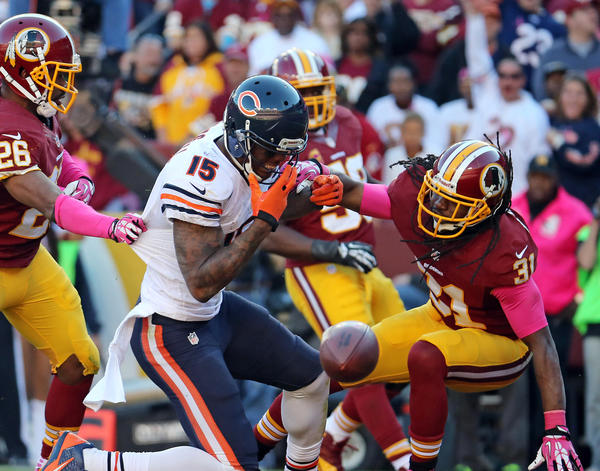 Chicago Bears wide receiver Brandon Marshall takes a hit from Washington Redskins strong safety Brandon Meriweather as the ball is knocked away in the end zone in the fourth quarter on Sunday, Oct. 20, 2013 at FedEx Field.