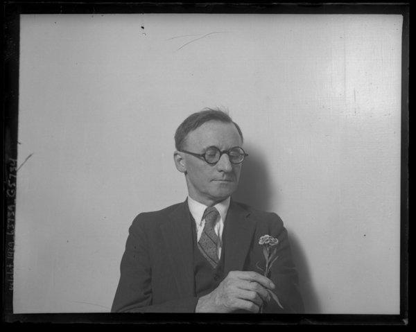 Dr. Thomas W. Young seen from waist up, holding a flower in Los Angeles in 1925