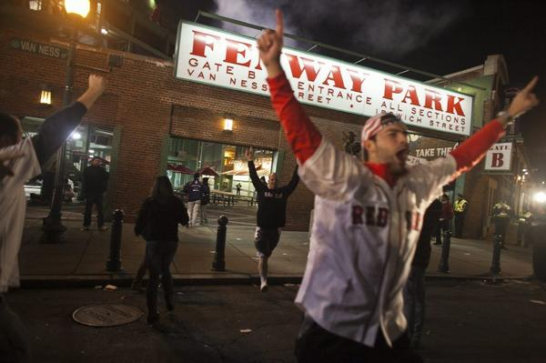 Fans rush out of Fenway Park after the Red Sox won the World Series in Boston on Wednesday.