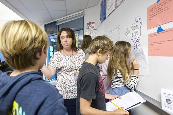 Kelly Skon, center, answers a question for Dylan Brashier, left, as members of his group, Charlie Besso and Cameron Russo, work on solving a problem during a pre-algebra class at Thurston Middle School on Oct. 25.