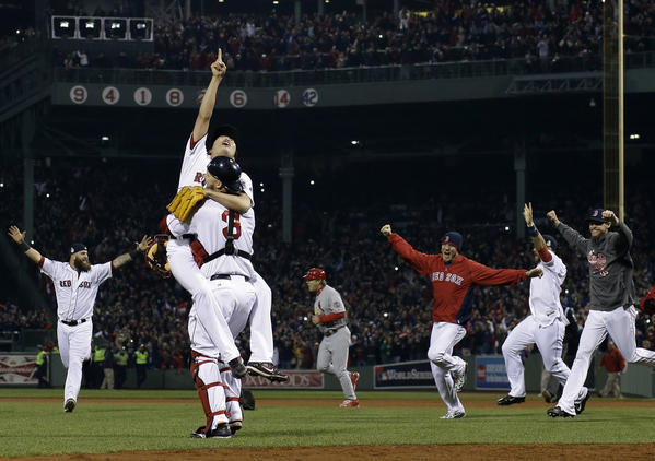 Boston Red Sox relief pitcher Koji Uehara and catcher David Ross celebrate after getting St. Louis Cardinals' Matt Carpenter to strike out, ending Game 6 of baseball's World Series. The Red Sox won 6-1 to win the series.