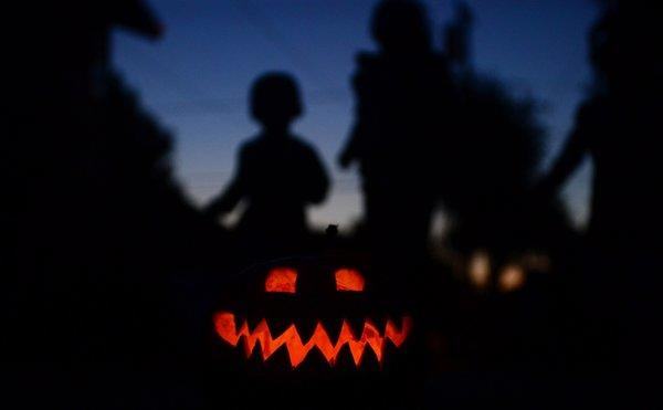 Children play behind a pumpkin carved and lit for Halloween in Monterey Park.