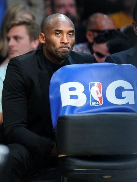 Kobe Bryant sits behind the Lakers' bench during the team's season opener against the Clippers at Staples Center on Tuesday.