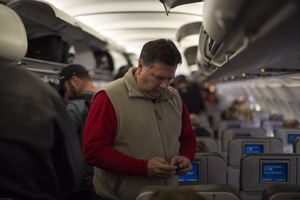 A Jet Blue passenger checks his cellphone.