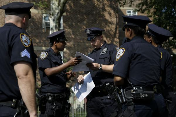 New York police officers take a report from a woman whose phone was stolen in the Brownsville section of Brooklyn.