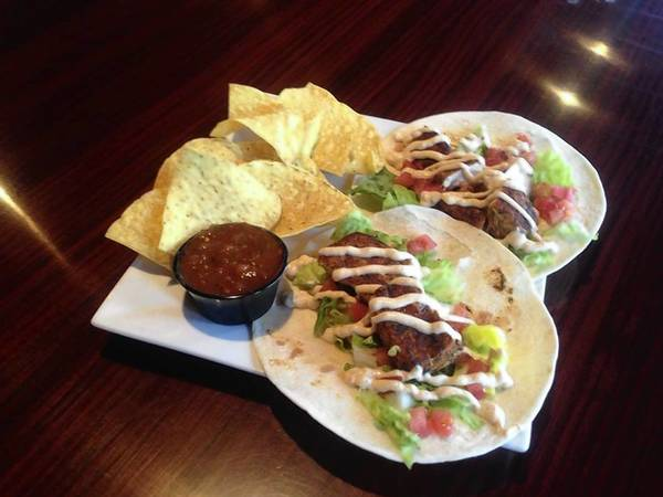 The blackened mahi tacos are stuffed with lettuce, tomato and drizzled with a Cajun sour-cream sauce.