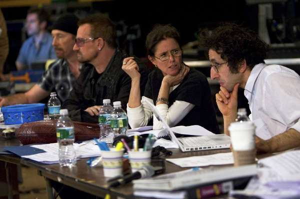 "Glen Berger, right, conferring with Julie Taymor in 2009 during rehearsals for the musical ""Spider-Man: Turn Off the Dark"" in New York. At left are U2 members the Edge and Bono."