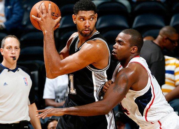 Spurs power forward Tim Duncan works in the post against Hawks power forward Paul Millsap during a preseason game.