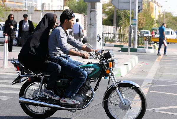 Iranian youths ride a motorcycle to bypass chronic traffic in central Tehran on Oct. 17.