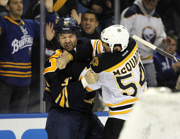 Sabres defenseman John Scott and Bruins defenseman Adam McQuaid fight during the third period.