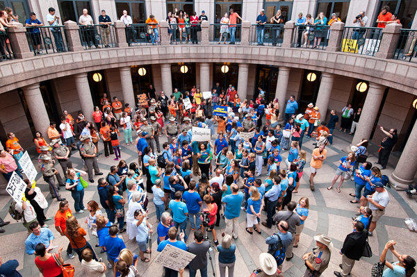 Texas State Troopers separate protesters in orange from blue-clad supporters rallying in July for a bill proposing limitations to abortion in Texas.
